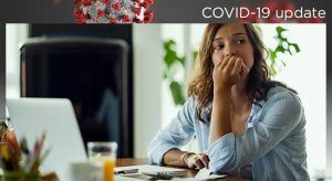 A woman sits at her home office looking off into the distance, illustrating 'how long after exposure to test positive for COVID-19'
